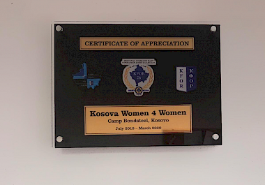 KW4W accept a certification of appreciation from Camp Bondsteel